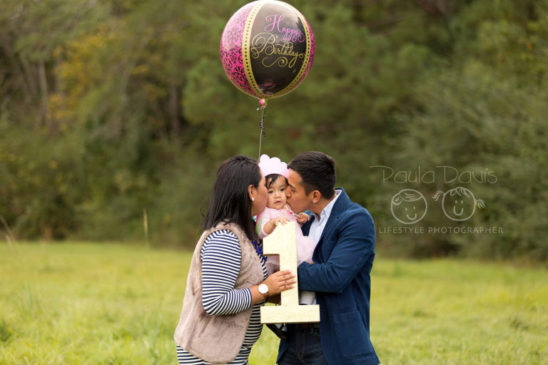 mom and dad kissing baby girl