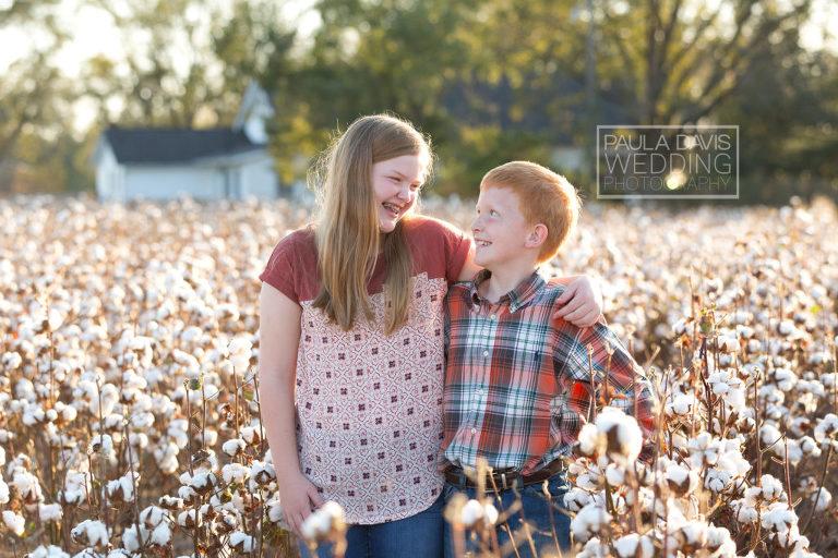 siblings smiling in cotton field