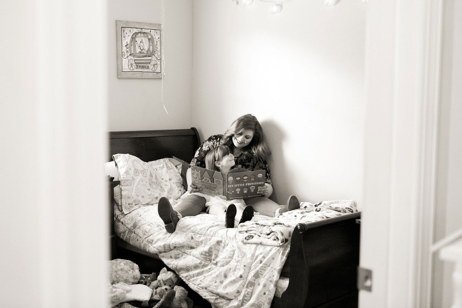 mom holding daughter on her bed while reading a book
