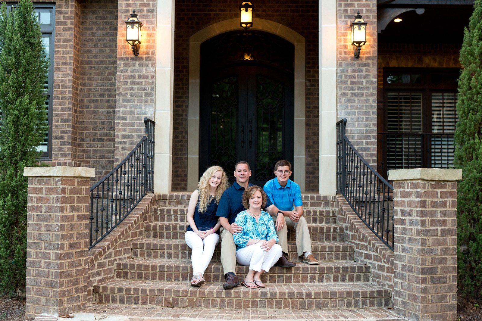 family sits together on the front steps of their home