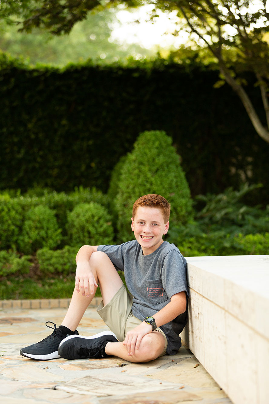 boy sits near the jules collins smith museum of fine art gardens