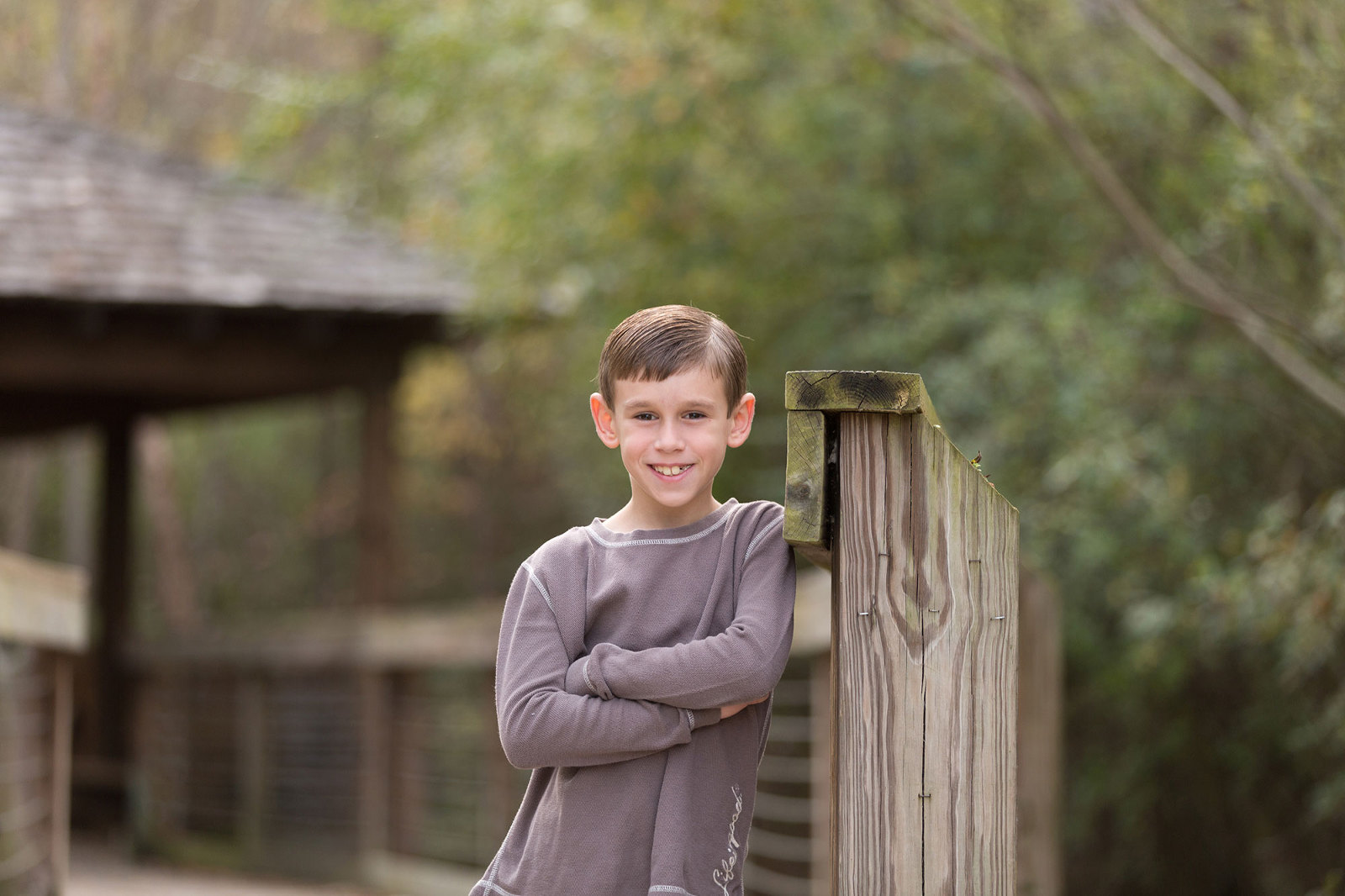 young boy stands near a bridge at town creek park
