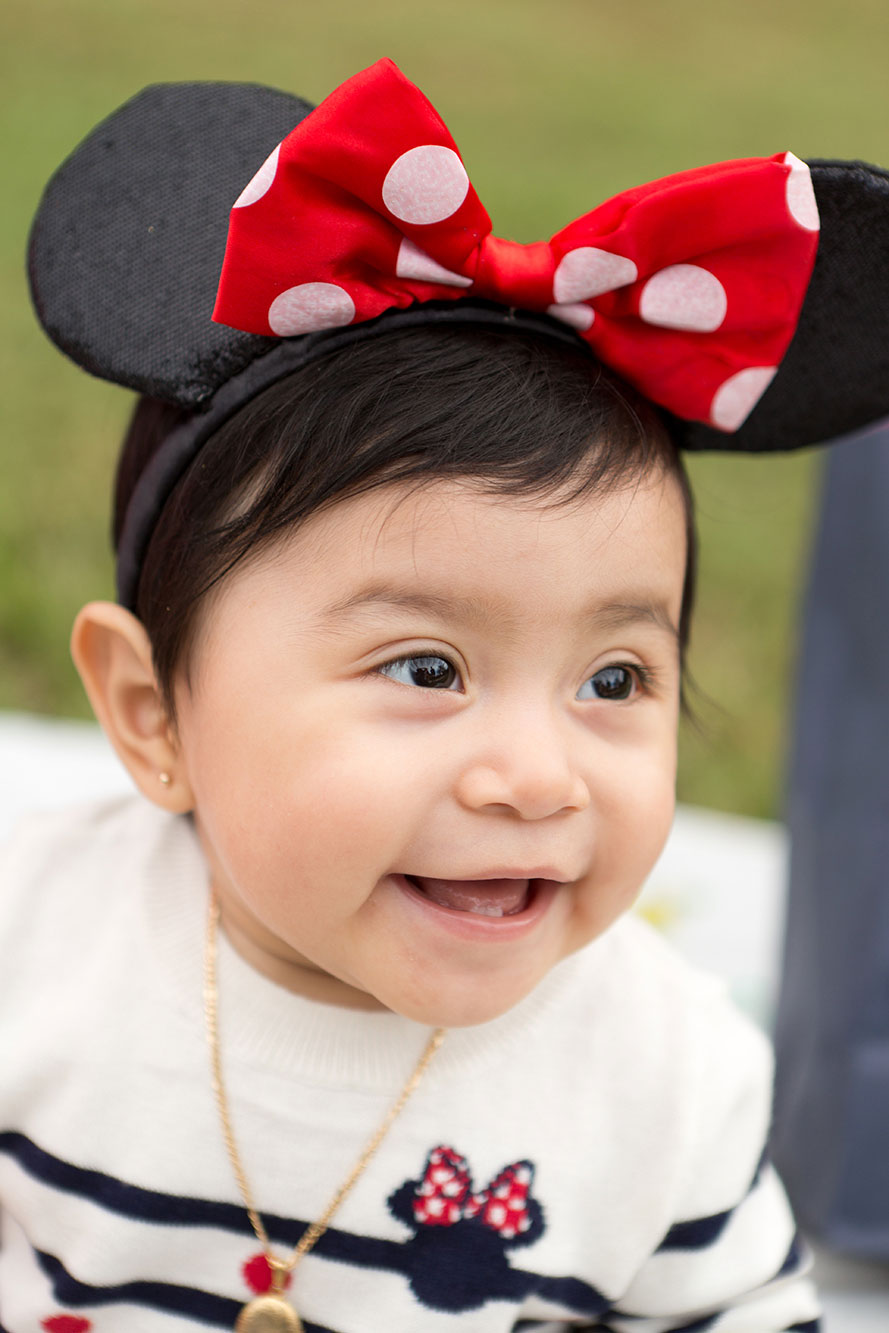little girl wears mouse ears and smiles