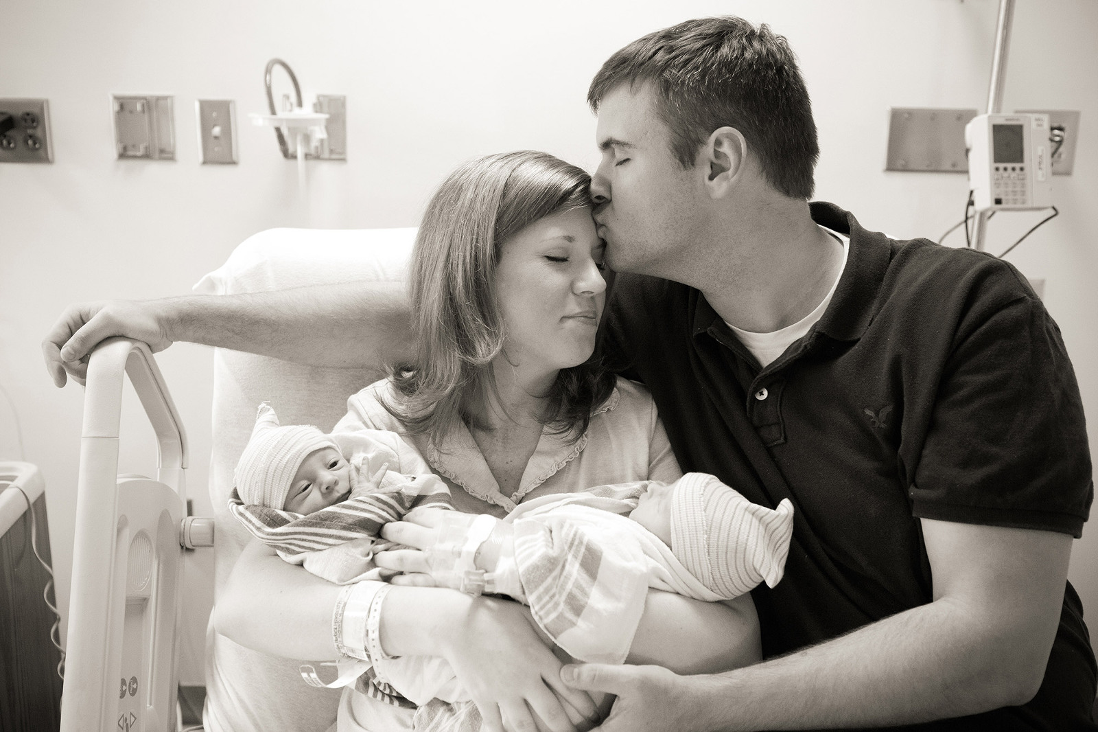 dad kisses mom on head while she holds newborn baby twin girls