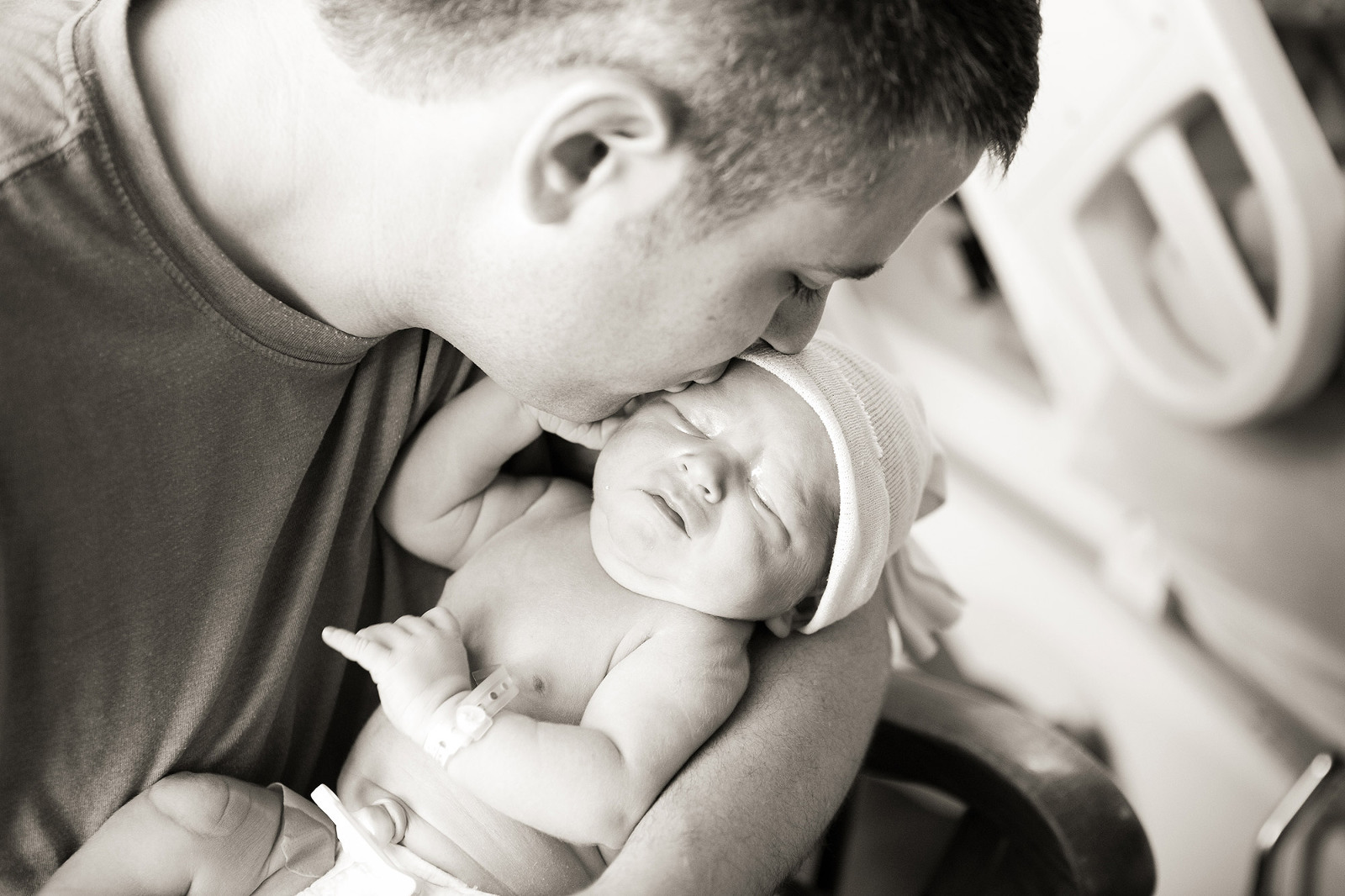 dad holds newborn son and kisses his head
