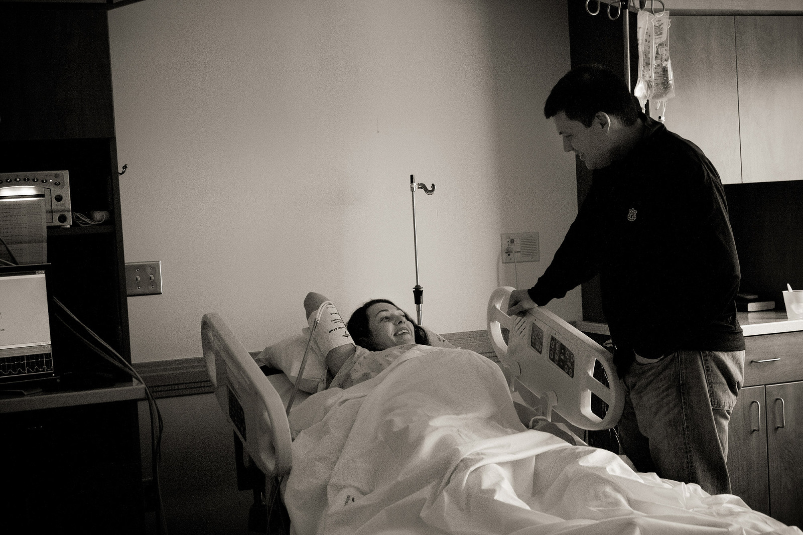 dad talks to mom while she labors in hospital bed