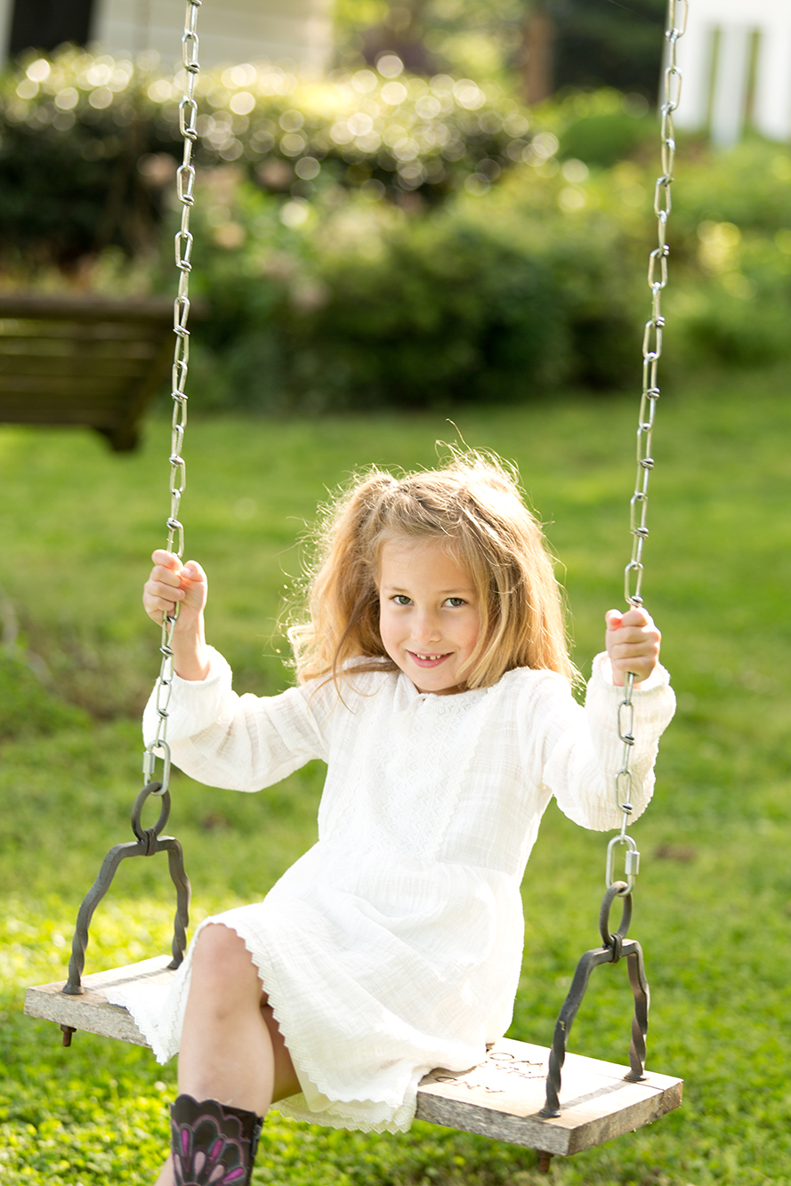 girl on swing with backlit sun