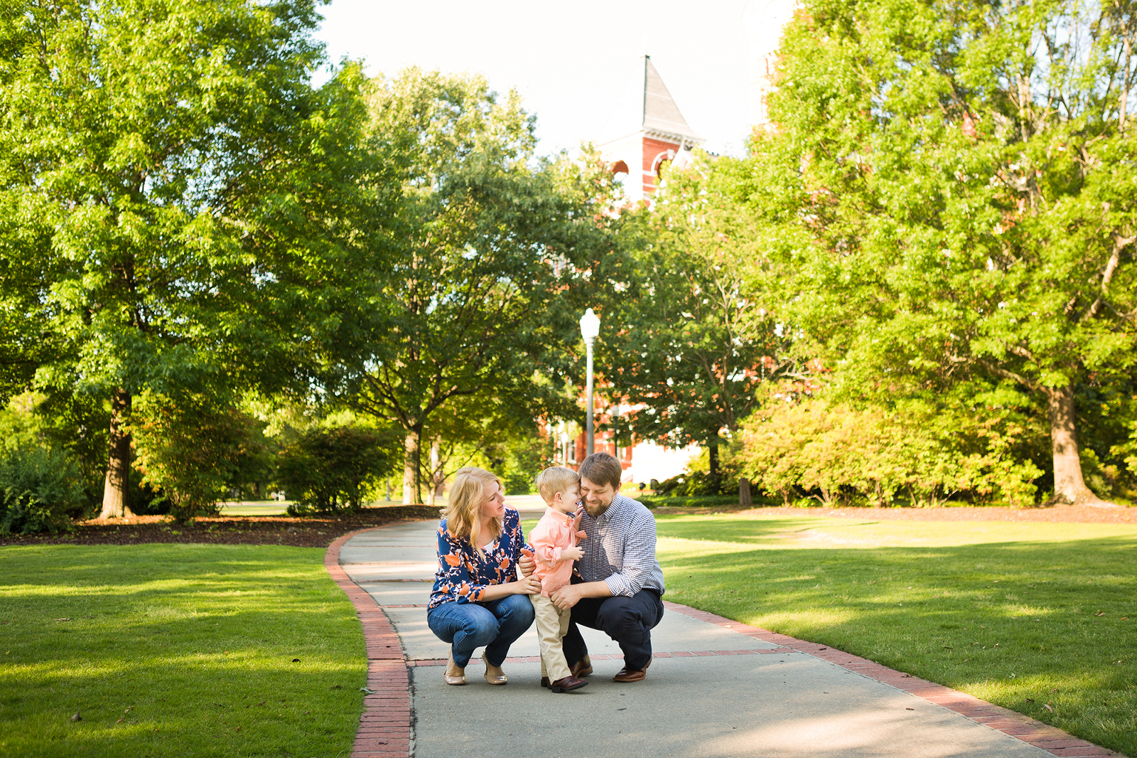family with young son on a sidewalk near Samford hall in auburn