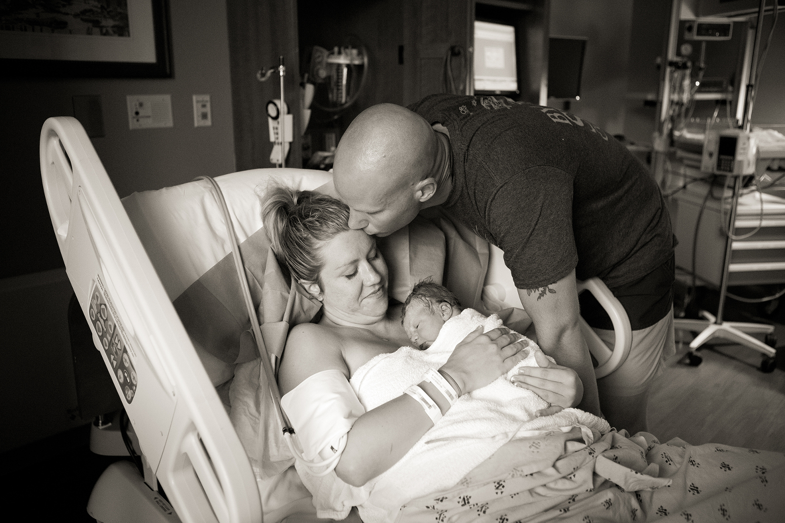 dad kissing mom in hospital bed on the head after the birth of their son