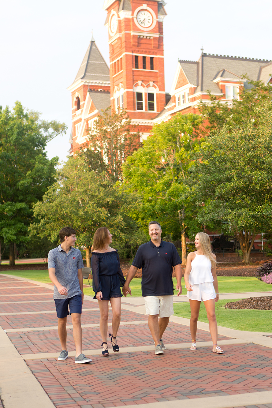 family walking on sidewalk near samford hall in auburn