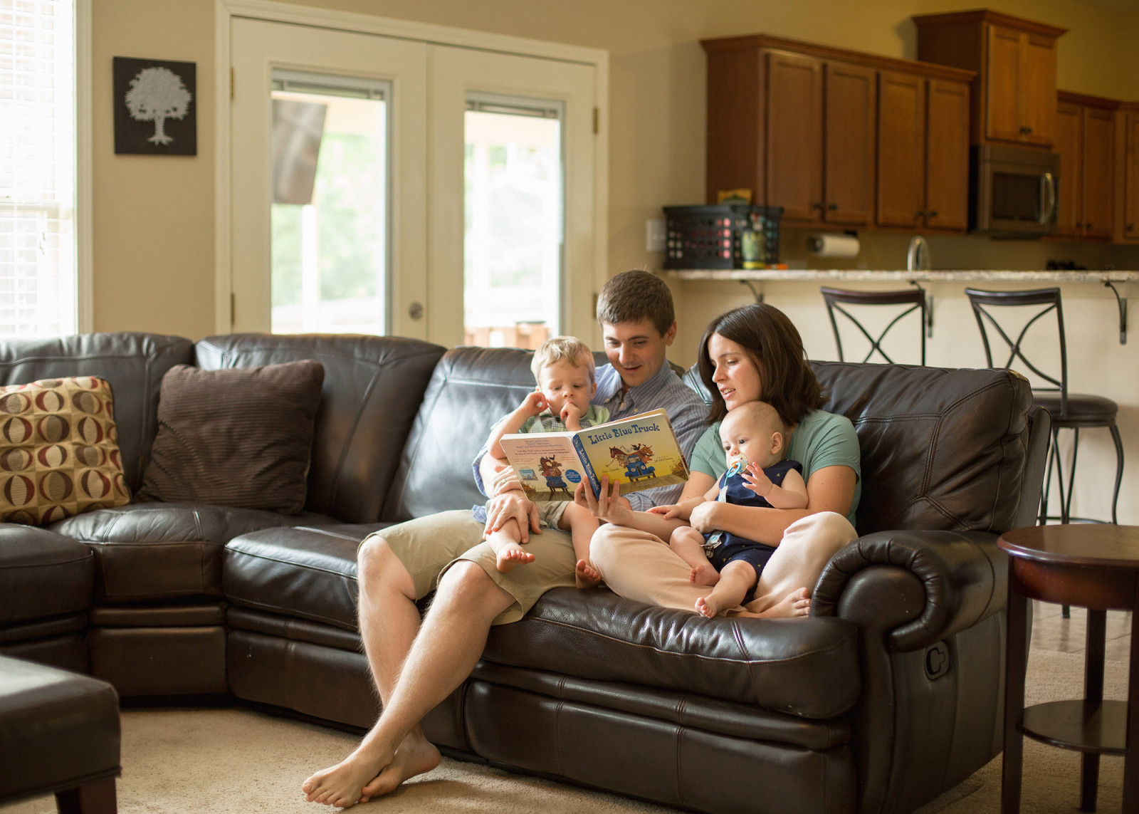 family sitting together on a couch reading a book