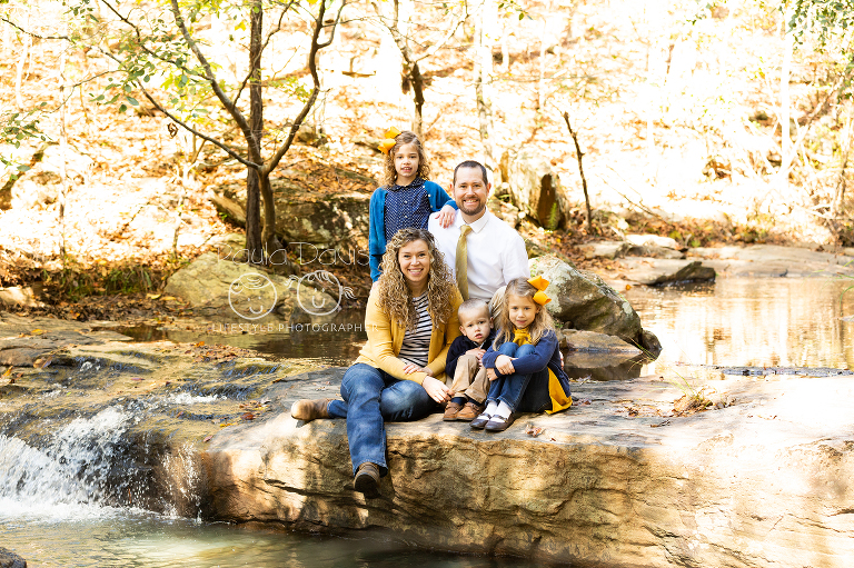 family sitting near a small waterfall during fall