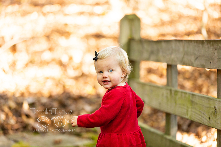 little girl in a red dress running on a small bridge