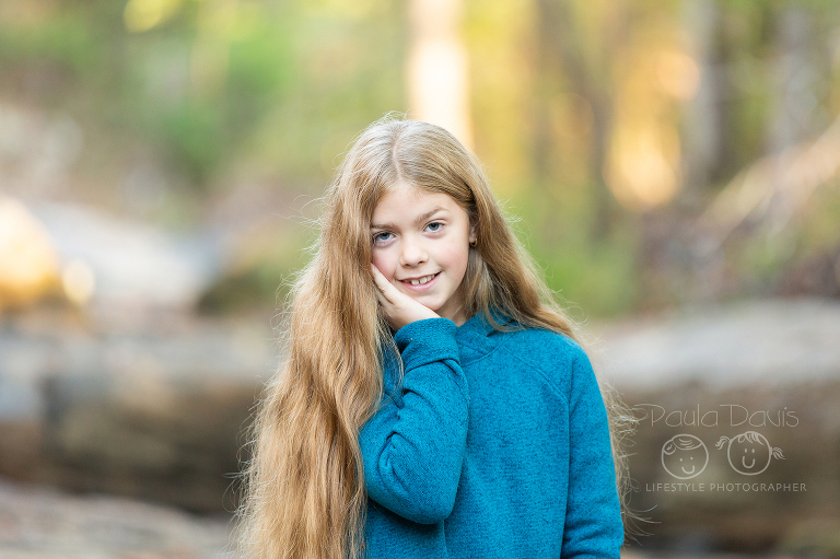 young girl with long hair standing near trees