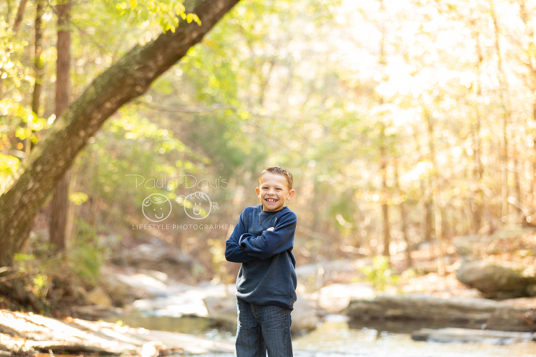 young boy standing with his arms crossed in a creek