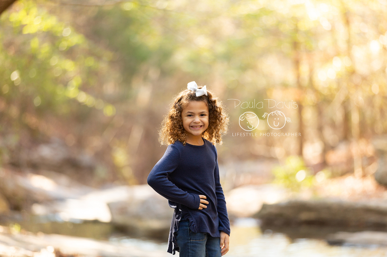 young girl standing in a creek