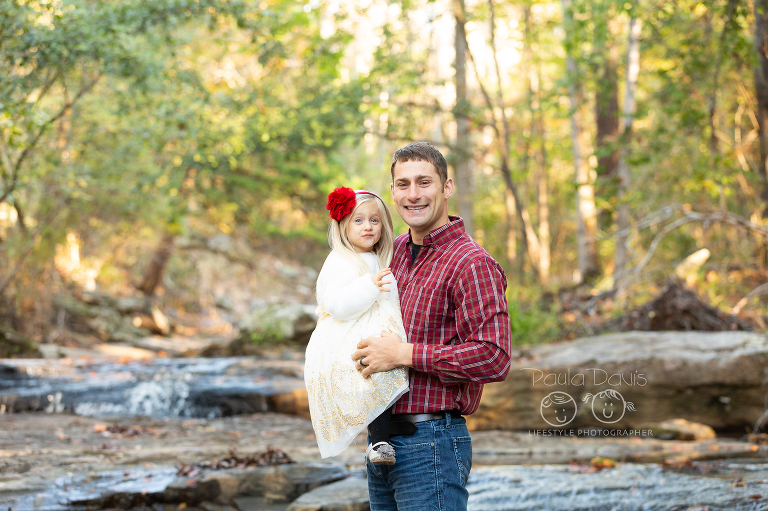 dad holding his youngest daughter in a creek
