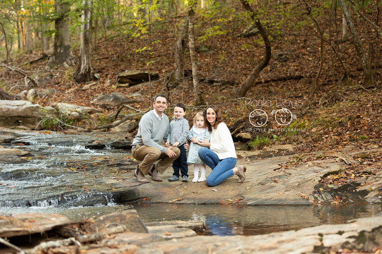 family kneeling together on rocks in a creek