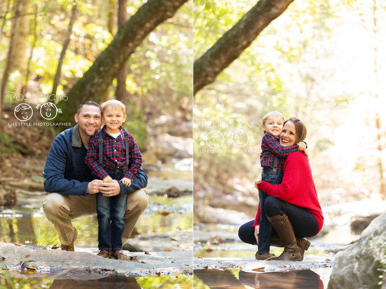 parents holding their son during portraits in a creek bed