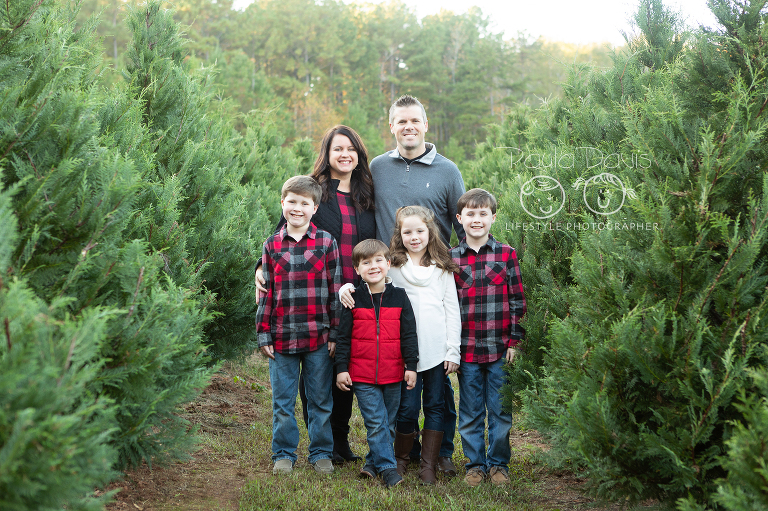 family standing together in a christmas tree farm