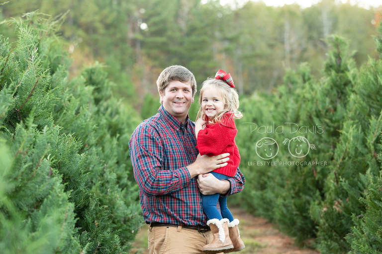 dad holding his daughter in a row of christmas trees