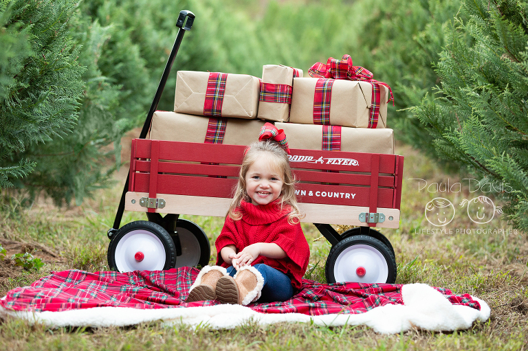 girl sitting next to radio flyer wagon full of presents in a christmas tree farm