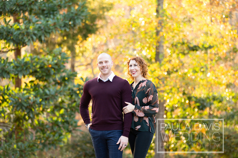 couple standing together near fall leaves