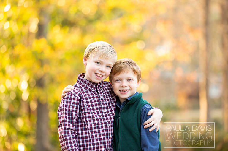 brothers hugging closely during fall