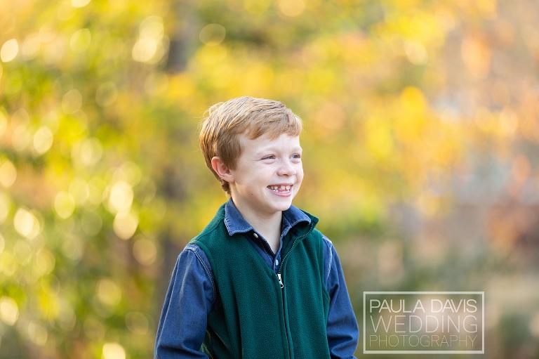 boy wearing a vest smiling big