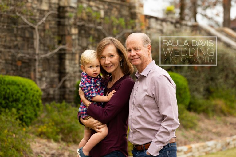 grandparents posing with their grandson in their yard on lake martin