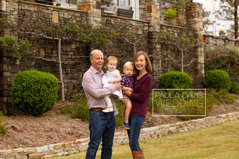 grandparents posing with their grandchildren beside lake martin