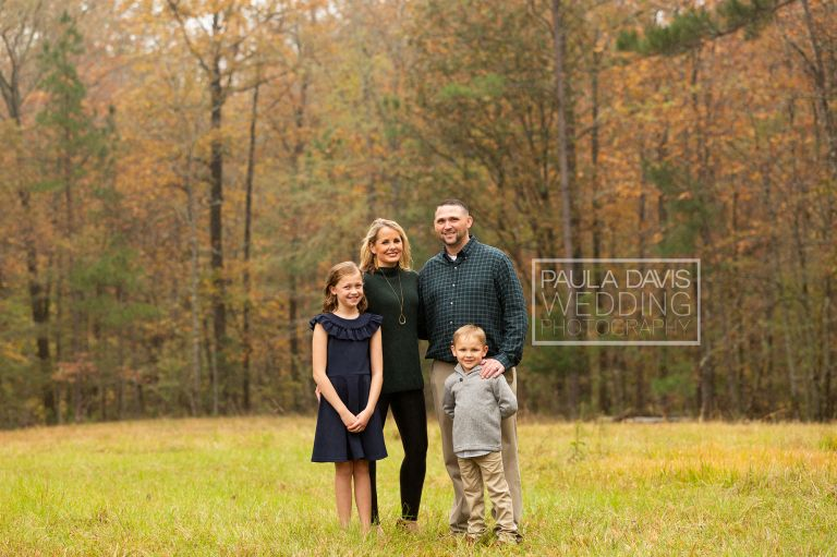 family portrait in a field next to woods in the fall