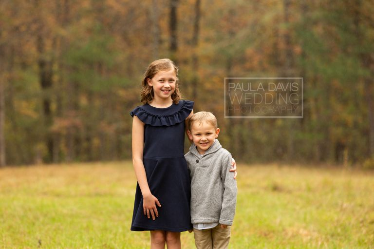 brother and sister in a field next to woods in the fall